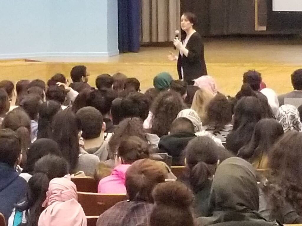 Jessica onstage talking to a large group of students