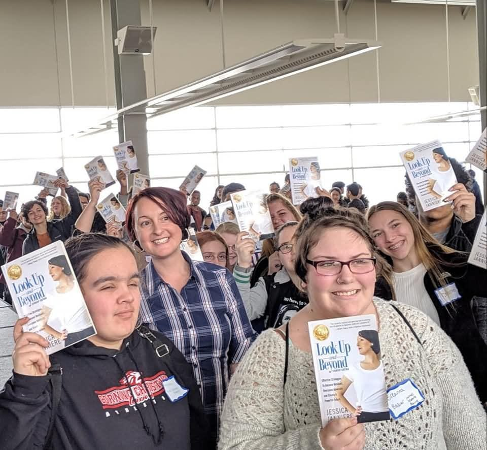 A group of smiling students holding up Jessica's book, Look Up & Beyond